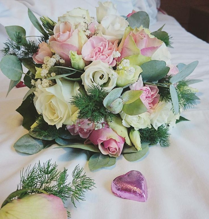 Wedding bouquet in pale pink, white and greens. Roses, carnations and eucalyptus.