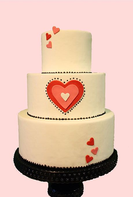 Brides.com: Heart-Themed Wedding Cakes. Pink and Red Hearts Wedding Cake. Cute and just to the left of traditional, this heart-adorned cake with black dotted accents from The Hudson Cakery is a loving accent to any style of wedding.  Browse cakes for a casual wedding.