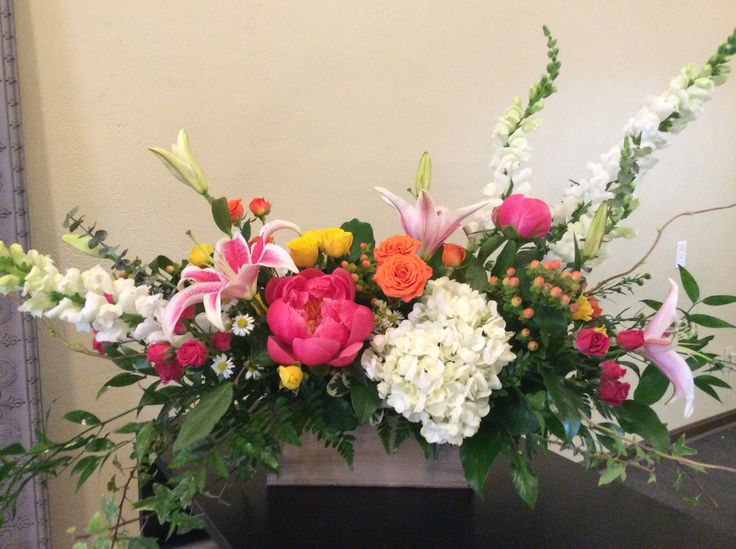 Wooden box of lilies, peonies, hydrangea, snapdragon, and roses.