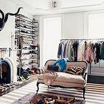 Chic closet design with stone fireplace, gray walls paint color, modern pendant chandelier, white & gray striped rug, ivory & black linen French settee sofa, shoe rack and clothes rack.