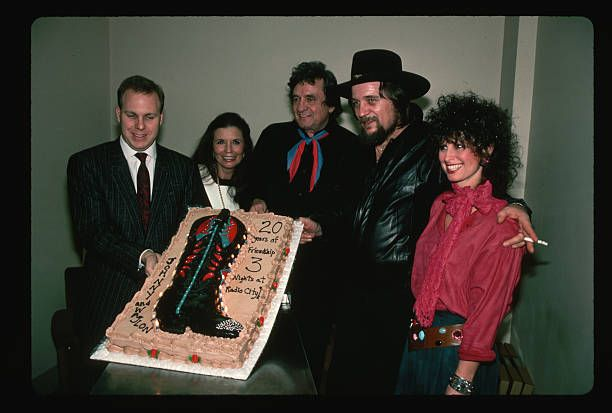 A man presents country legends Johnny Cash and Waylon Jennings a cake with a cowboy boot backstage at on of their concerts together at Radio City...