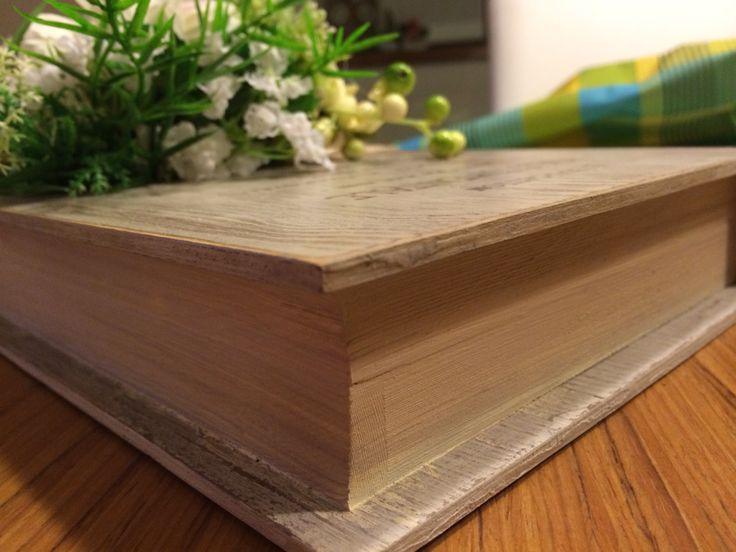 Libro in legno con composizione di fiori.