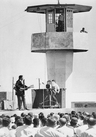 """10 Apr 1969, Cummins, Arkansas, USA --- Country and western singer Johnny Cash, at microphone, puts on a show 4/10 for about 800 inmates at the Cummins Prison Farm and guests. He adapted his famous for the crowd, that included Arkansas Governor Winthrop Rockefeller, and sang """"I'm locked in Cummins Prison."""" Cash was made an honorary """"life-termer."""""""