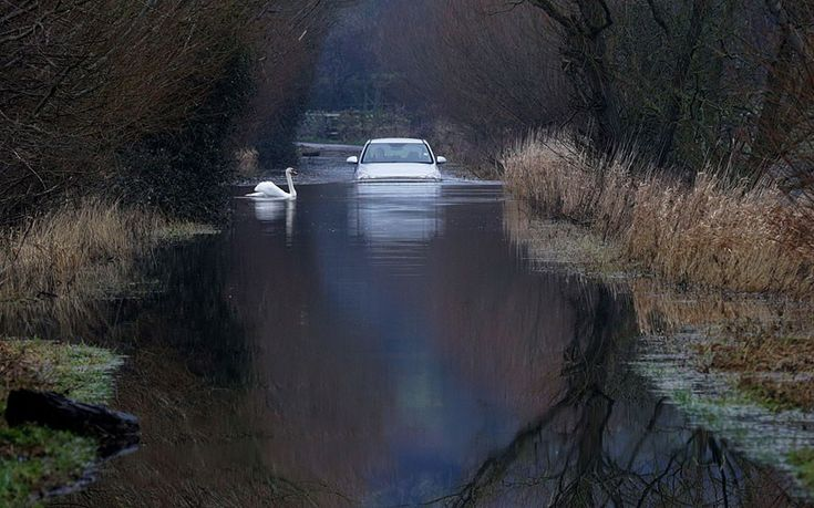 A car drives through flood water on the Somerset Levels near Langport.
