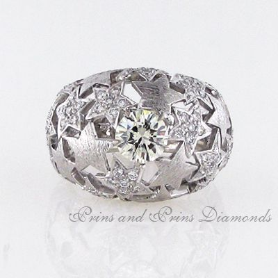 The centre stone is a 1.05ct M/SI1 round brilliant cut diamond claw set in 18k white gold with 0.62ct round brilliant cut diamonds pavé set in a star design