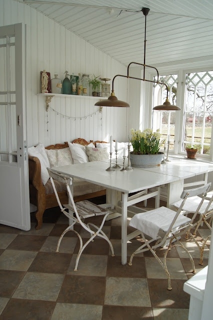 Screened in porch, light fixture, white paneling, table arrangement