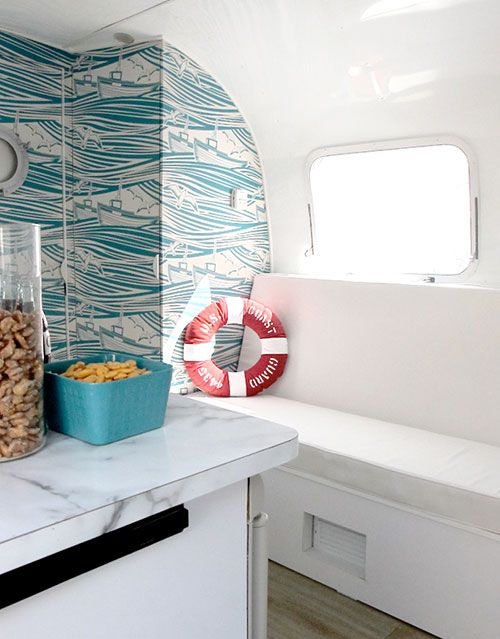 """Sneak Peek: Amelia the Airstream. """"For the days when it's too cold or too wet to go hiking or biking we installed an under the counter dvd player to get our fill of old movies. The camper is super cozy to cuddle up for a movie, and the sound of the rain on the metal roof adds to the ambiance of """"roughing it!"""""""" #sneakpeek"""