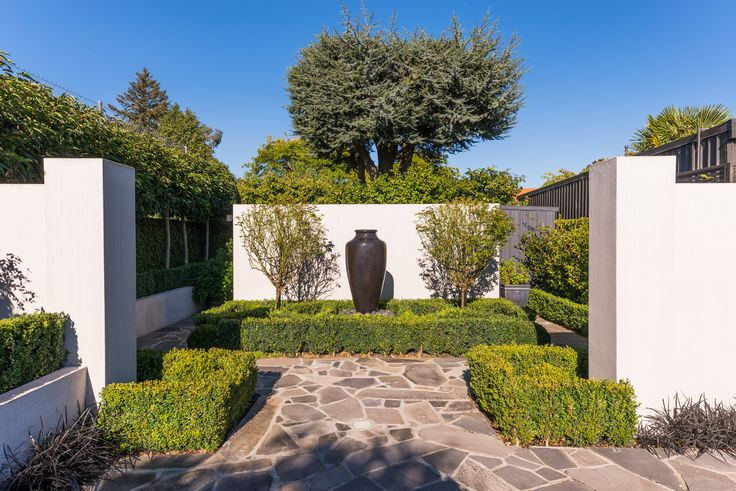 The over-sized pot doubles as a water feature and draws the eye to the centre of this outdoor space