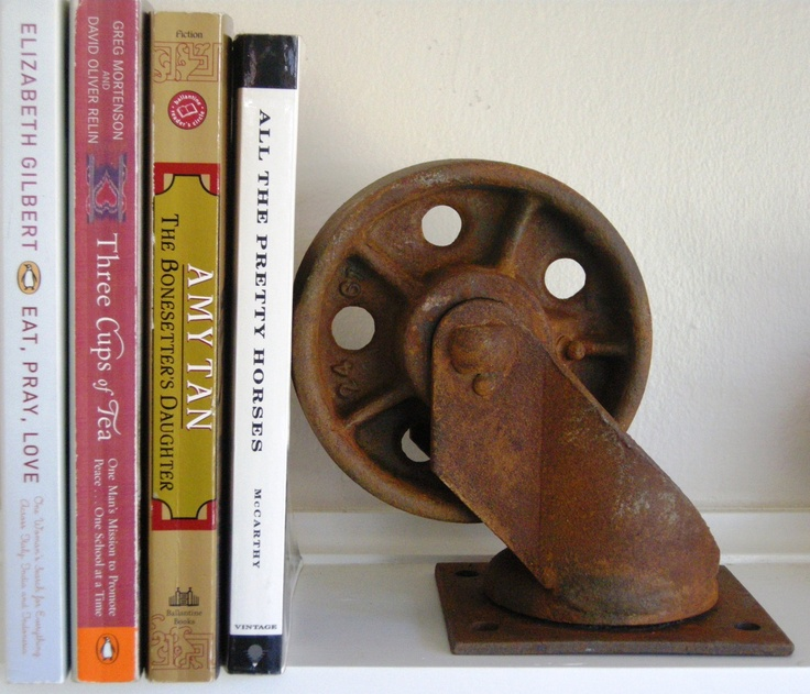 It's rusty, it authentic and I love it! Salvaged Industrial Metal Swivel Caster Wheel used as bookend