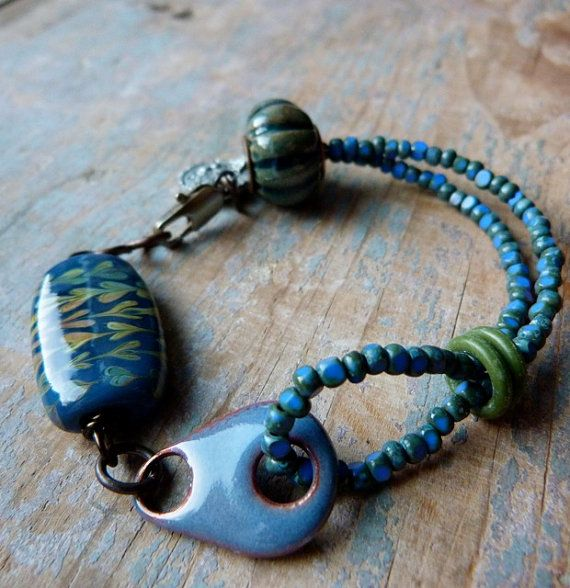 By Lorelei Eurto. Ceramic round by Gaea, lampwork by loupiac, rubber o-rings, enamel connector by ckoop, faceted Czech glass beads
