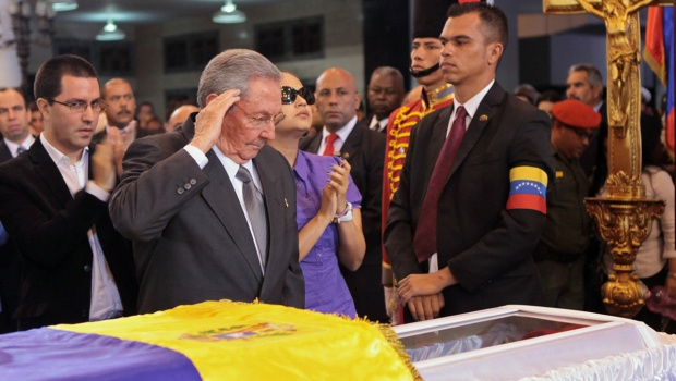 Cuban President Raul Castro salutes as he stands next to the coffin containing the body of the late Venezuelan President Hugo Chavez, during his wake at a military academy in Caracas, Thursday, March 7, 2013.