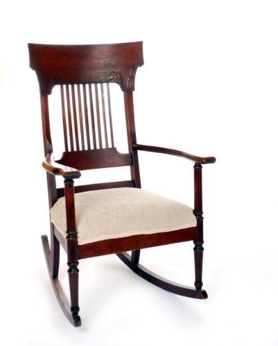 A big help in identifying old rocking chairs is to look at the lines and the way the back is designed. This neoclassical, upholstered rocker is part of the Colonial Revival period from 1870-1920. It has some detail in the back as well as the spools on the legs. You can see some of the simple Arts and Crafts era influence in how the back of the chair is made.