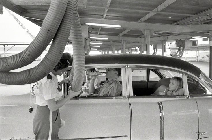 1957. Getting cooled air piped into the car while enjoying a meal at a drive-in restaurant. Houston, Texas.