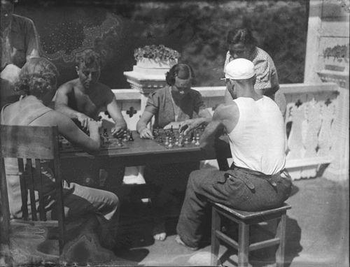 Naisia ja miehiä hellevaatteissaan pelaamassa shakkia Turun työväenopiston kesänviettohuvilan kuistilla. Kaksi- ja kolmikymmenluvuilla Ruissaloon ilmestyivät lastenhuollon järjestöt ja sivistystehtävän omaavat yhdistykset, jotka eivät kuitenkaan olleet ristiriidassa vakiintuneiden huvilanomistajien kanssa. Kuvaaja: Turun sanomat, 1937.  TS2733: