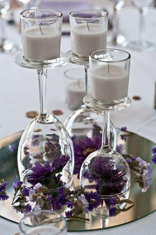 Centro de mesa con copas al revés, votivas con velas y un espejo de base.