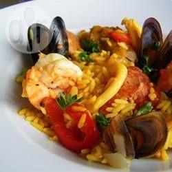 Een paella naar authentiek Spaans recept met chorizo, kip, erwtjes, inktvis, mosselen en garnalen. De saffraan en chorizo geven deze eenpansmaaltijd een prachtige rode kleur. Een speciale paellapan wordt aangeraden.