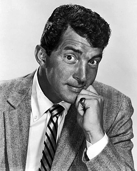 """Dean Martin ( June 7, 1917 – December 25, 1995) was a singer, film actor, tv star and comedian.  A member of the """"Rat Pack,"""" Martin was a major star in four areas of show business: concert stage/night clubs, recordings, motion pictures, and television.   Martin's relaxed crooning voice earned him dozens of hit singles including his signature songs """"Memories Are Made of This"""", """"That's Amore"""", """"Everybody Loves Somebody"""",""""Volare"""" and """"Ain't That a Kick in the Head?""""."""