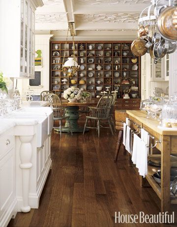 The antique oak cabinet, originally made for a French store, is perfect for a collector. Designer Susan Dossetter found the reproduction Windsor chairs in Nantucket and had the table made to work with the chairs and the cabinet in this kitchen. Co-designed by Andrew Skurman.