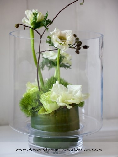 Minimal amount of flowers to create a lovely arrangement in a clear vase. Large leaf hides the foam oasis.