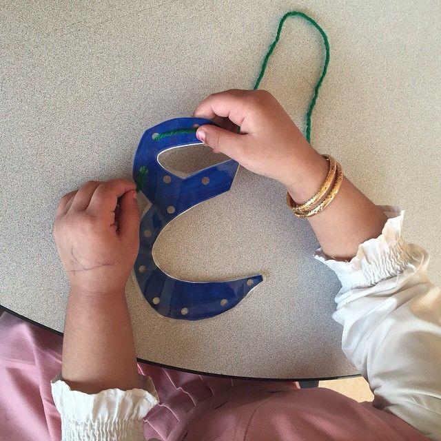 تغليف الحرف ثم تخريمه ليقوم الطفال بتقوية عضلات يديه وهو يمر الخيط بين الفتحات مع ترسيخ شكل الحرف
