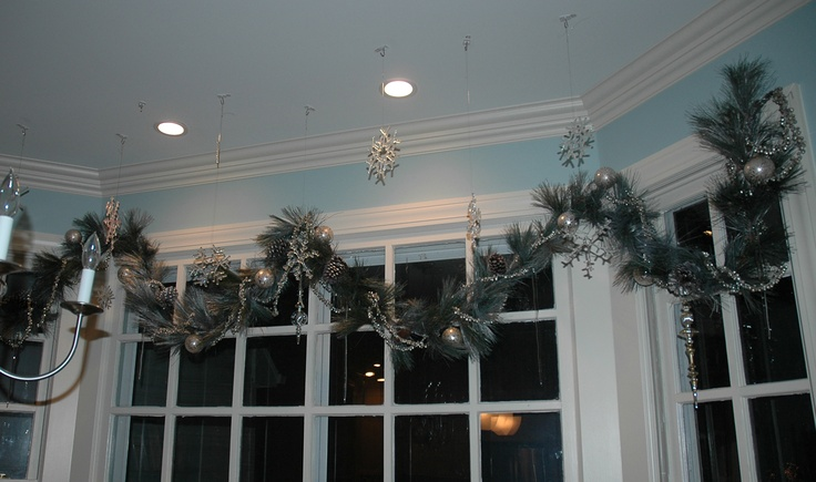 My garland in my kitchen window. bought 2 pine garlands at KMart for 12. spray painted them with primer, silver, and taupe glitter spray from michaels. Silver Bell garland from World Market, glass snowflakes from local glassmaker, now in Raleigh. I've been collecting them for many years. They do one new and different one each year.