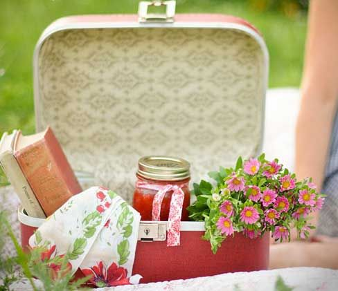 Picnic using a small train vintage case with jam, books, flowers and vintage linens.