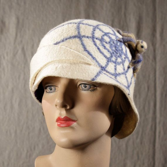 A white cloche hat with a 2D web and 3D needle-felted spider shades of cafe and light blue. The brim gradually folds and slims to a point attached to the right front of the crown. This hat can be made in any color you like. There is no upcharge for custom colors.  ***THIS HAT IS MADE TO ORDER. PLEASE SEND ME YOUR HEAD SIZE WHEN PLACING YOUR ORDER***  All of my hats are hand felted Merino wool from non- tail docked sheep.  The nature of hand felted wool means that there are many variables…
