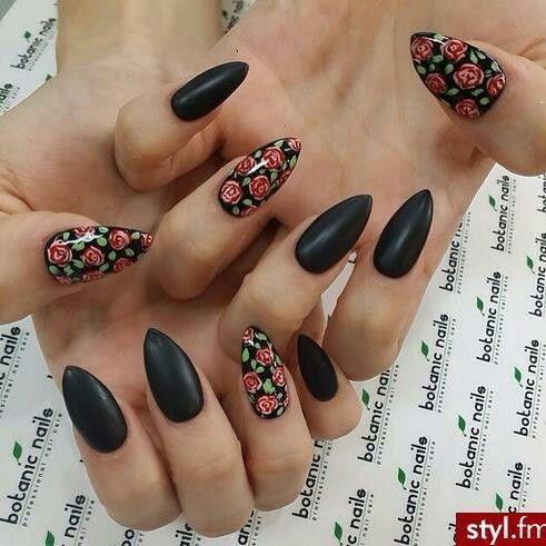 Hermosas uñas de forma almendrada en color negro, algunas de ellas decoradas con rosas rojas y hojas verdes.
