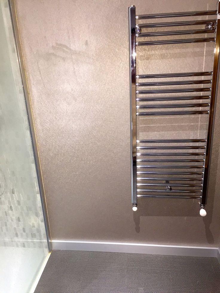 Detalle de baño con vescom en pared y pavimento lico en el suelo