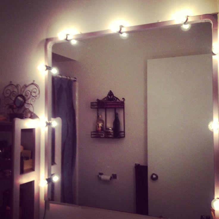 DIY vanity lighting with a string of bulbs and electrical cord hiders painted to match bathroom