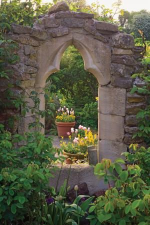 A salvaged Gothic window, part of a wall surrounding the sunken pool area built in 1998 at Hanham Court, the Bannermans' longtime home.     Terra cotta pots of tulips brighten the early spring garden while layers of cascading foliage give the illusion of a secret space.