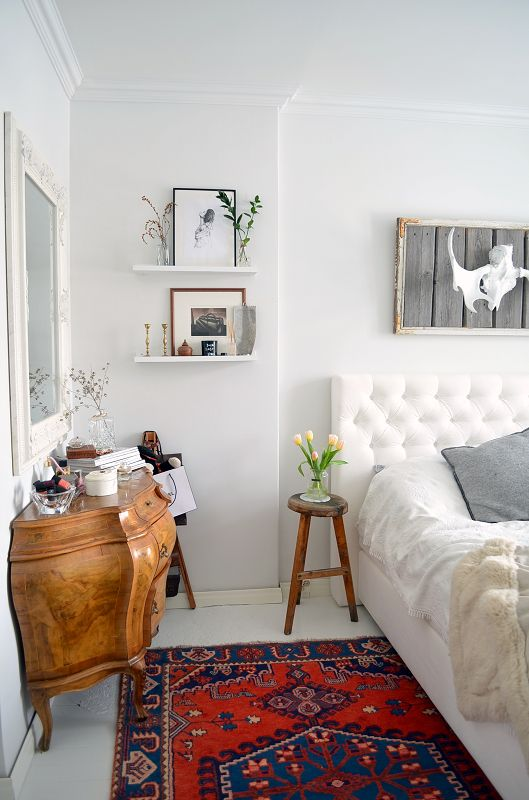 Bright eclectic bedroom with a bombay cabinet, stool nightstand, tufted headboard + moroccan rug!