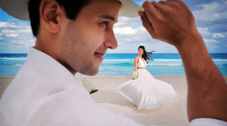 Fun portrait of groom with hat and twirling bride on the beach at their destination wedding in Cancun, Mexico | Palace Resorts Weddings ®
