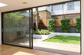Simple landscaped city garden with large sliding doors at the end of the house.