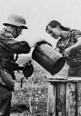 A Hungarian woman passing water to a soldier of the retreating German army. The Puszta/Hungary, autumn 1944.