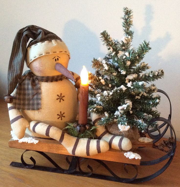 Large wood & metal sled featuring a vintage snowman, snowtex embellished minature tree and battery operated, wax dipped flicker candle.