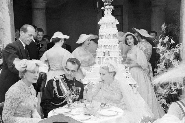 Il Principe Ranieri di Monaco e la neo principessa Grace al ricevimento del loro matrimonio il 19 aprile 1956. Sullo sfondo la torta di sei piani del peso di 150kg., con la riproduzione del Palazzo Reale in pan di spagna bianco e rosa e in cima, sorretta da due cherubini, la riproduzione della corona di Monaco.