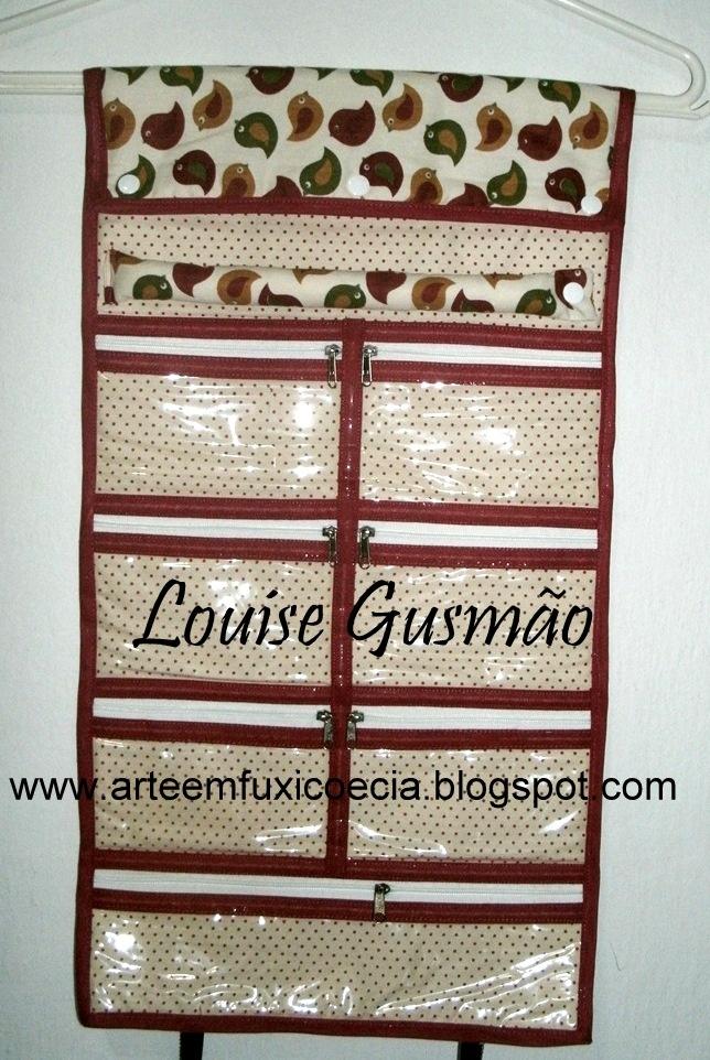 Porta Bijuterias - Interior - Bolsos para brincos e porta anéis, com alça para pendurar no cabide.