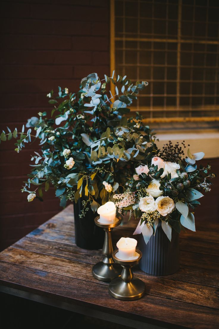 DY.o events (aka Duo)  Grey greens and soft white foral arrangements with candles. Wedding Present table floral arrangements.