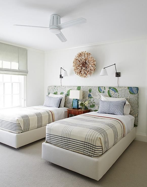 Fabulous shared boys' bedroom features twin beds on one shared headboard flanking a shared nightstand a peacock blue lamp under a light brown juju hat illuminated by swing arm wall sconces.