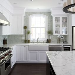 White cabinets, marble counter tops, subway tiles with a touch of green, and arch window, Wolf range. Just perfect.