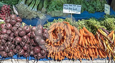 Bunches of fresh home grown carrots, beetroot and spring onions on a market stall.