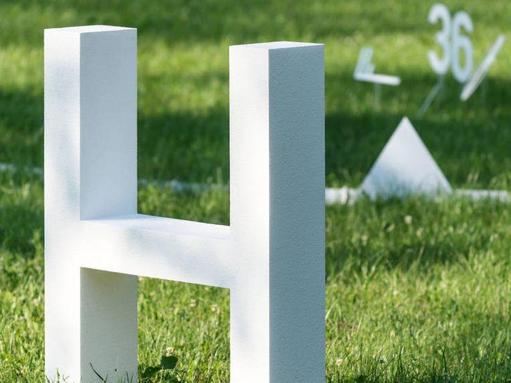 Ein weißes H steht mit weiteren Symbolen einer Wetterkarte auf einer Rasenfläche. Zusammen bilden sie die begehbare Wetterkarte des 5. Juli 2015 – dem bislang heißesten Tag in Deutschland seit Beginn der Wetteraufzeichnungen.