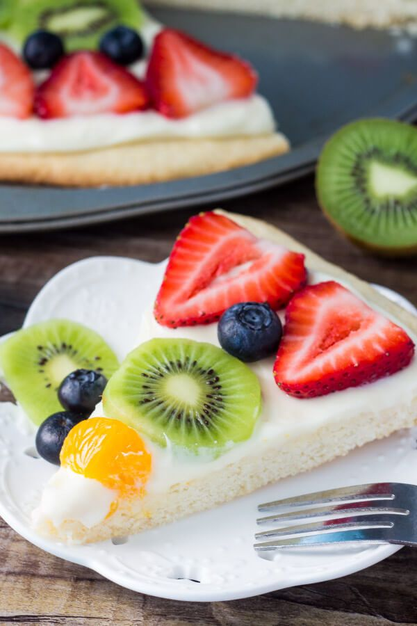 This sugar cookie fruit pizza has a soft & chewy cookie crust, a layer of smooth & tangy cream cheese frosting, and tons of fresh berries. Way easier than making pies or tarts, it's the perfect dessert for summer.