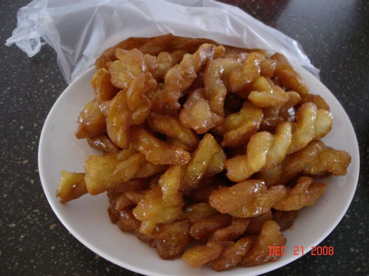 """A koeksister (or koe'sister) derives from the Dutch word koekje, which translates to """"cookie"""". It is a South African syrup-coated doughnut in a twisted or braided shape (like a plait). It is prepared by deep-frying plaited dough rolls in oil, then dipping the fried dough into cold sugar syrup. Koeksisters are very sticky and sweet and taste like honey."""