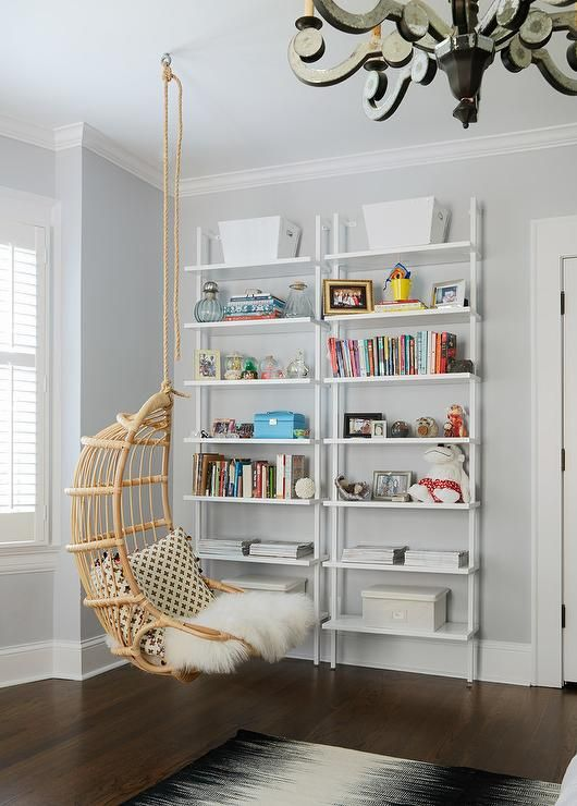 A Two's Company Hanging Rattan Chair hangs over a black and white rug in front of a two side by side white ladder bookshelves positioned in front of light gray walls lined with white crown molding in this stylish, well appointed teen girl's bedroom.