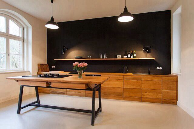 Great simple kitchen design with black wall and honey wood cabinetry.
