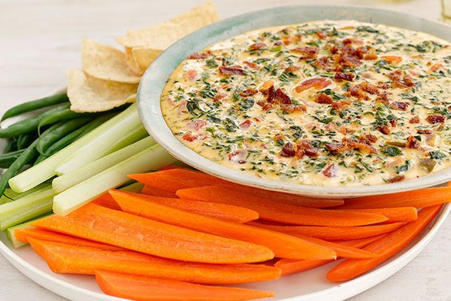 Kick off your next party with our zippy dip in your starting lineup. Chilies bring the heat while cheese, spinach and bacon assist on special teams for a potluck score!