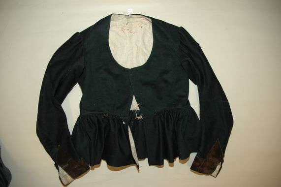 Rukketrøye i svart klede. - Rukketroye (jacket, I think) made in black cloth (wool). Two different types of fabric, since one has turned a bit green. There's velvet cuffs, and it's lined in cotton.