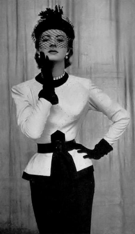 1950 Model in black wool skirt worn with a white silk top bordered in black and studded with diamonds, the small veiled toque completes the look, by Jacques Fath